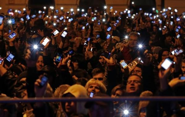 People hold up their mobile phones as they protest against a new tax on Internet data transfers in the centre of Budapest